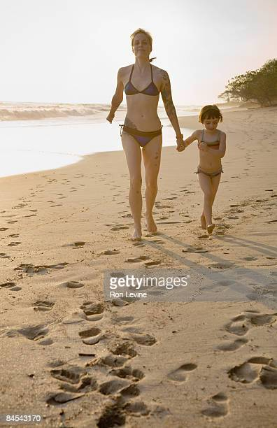 Mother and daughter running on the beach at sunset