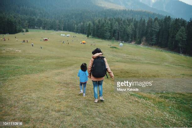 mother and daughter running over the slope - 松林 ストックフォトと画像