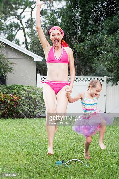 Mother and daughter running through sprinkler