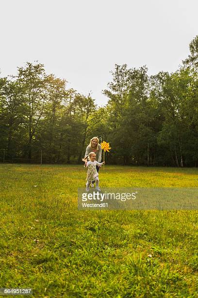 Mother and daughter running with paper windmill on meadow