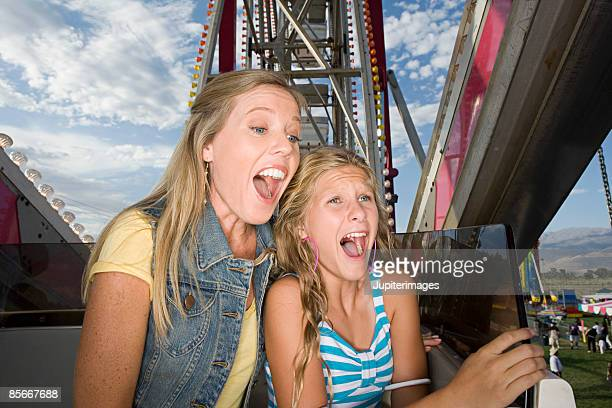 mother and daughter screaming on ride - girls open mouth stockfoto's en -beelden