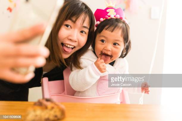 mother and daughter selfie on birthday celebration - happybirthdaycrown stock pictures, royalty-free photos & images