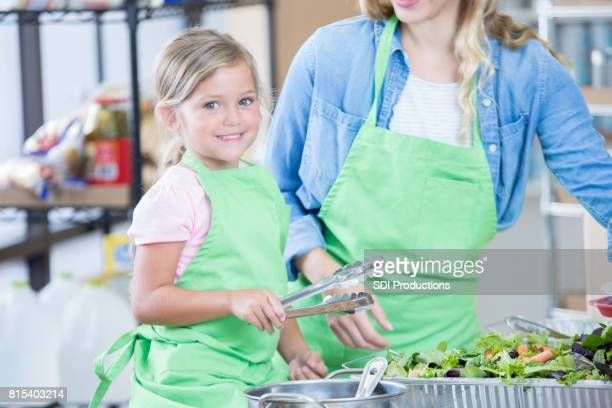 Mother and daughter serve healthy meals at soup kitchen