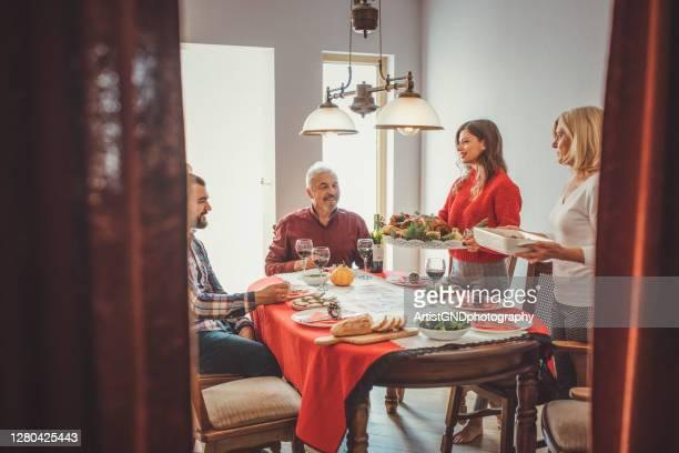 madre e figlia che servono pasto e tacchino di natale sul tavolo. - gruppo medio di persone foto e immagini stock