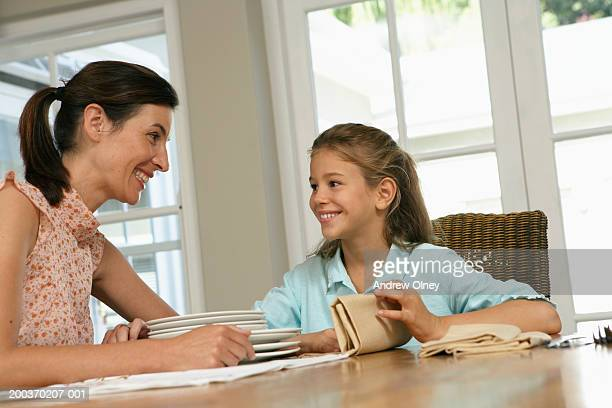 Mother and daughter (7-9) setting dining table, smiling