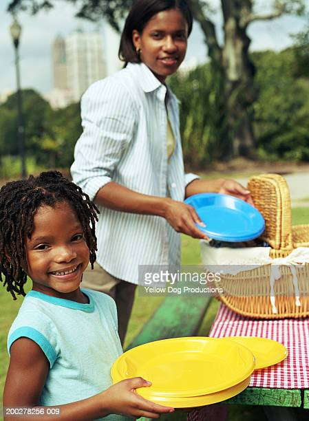 Mother and daughter (8-10) setting out plates at picnic