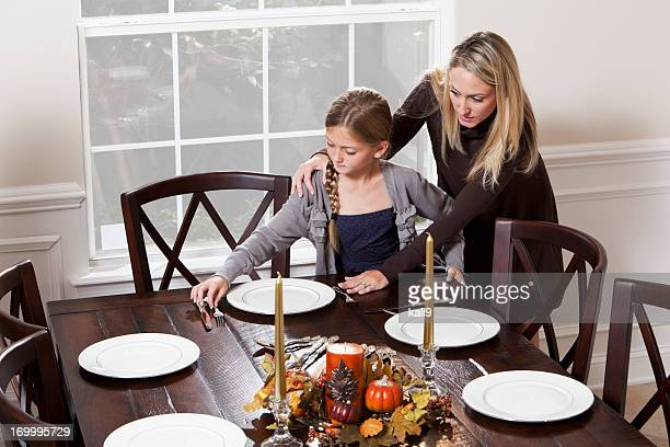 Mother and daughter setting table for dinner