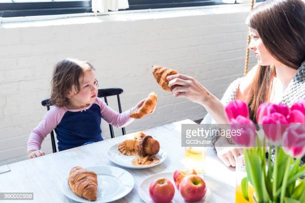 Mother and Daughter sharing croissant on a breakfast table