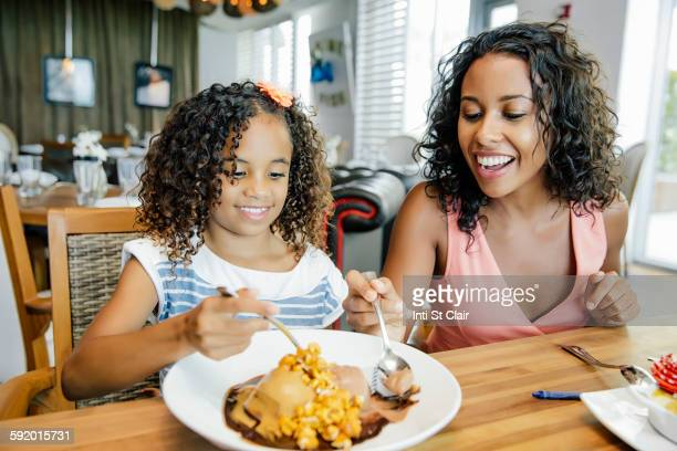 Mother and daughter sharing dessert in restaurant