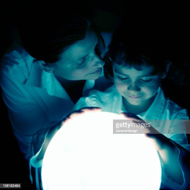 Mother and Daughter Sharing Moment with Glowing Globe