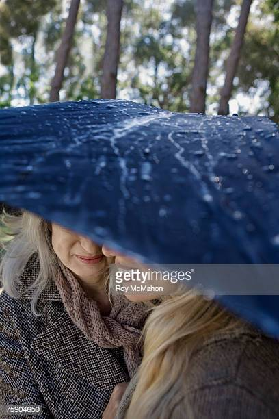 Mother and daughter sheltering under umbrella, outdoors