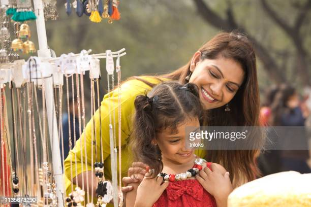 mother and daughter shopping for necklace - necklace stock pictures, royalty-free photos & images