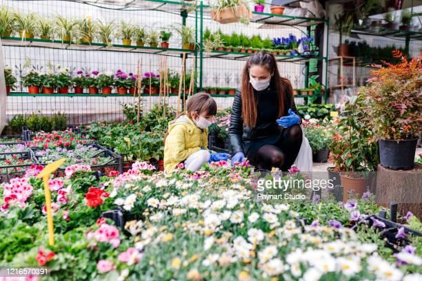 moeder en dochter die van bloemwinkel winkelen - beschermend masker werkkleding stockfoto's en -beelden