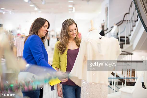 mother and daughter shopping in a clothing store - prom dress stock pictures, royalty-free photos & images