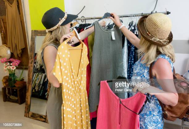 mother and daughter shopping in clothes shop - jurk stockfoto's en -beelden