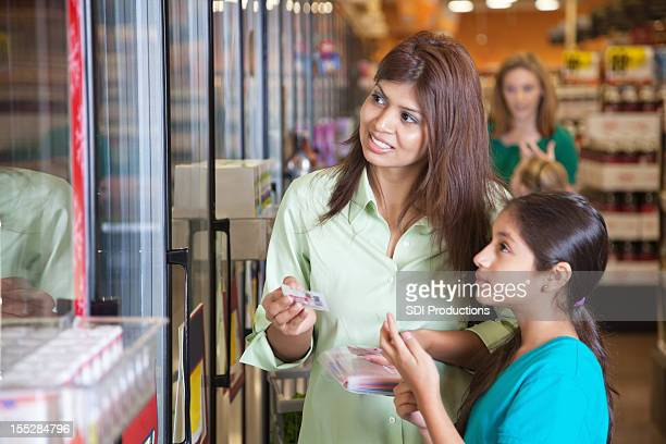 mother and daughter shopping with coupons at the grocery store - coupon stock photos and pictures