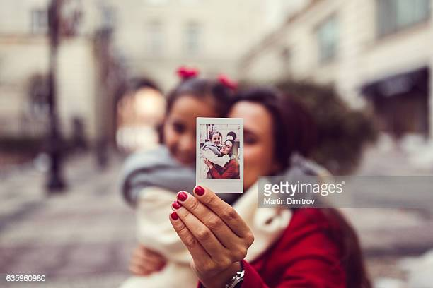 Mother and daughter showing instant photo