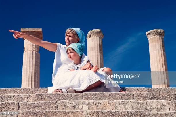 mother and daughter sightseeing lindos acropolis in greece - lindos stock photos and pictures