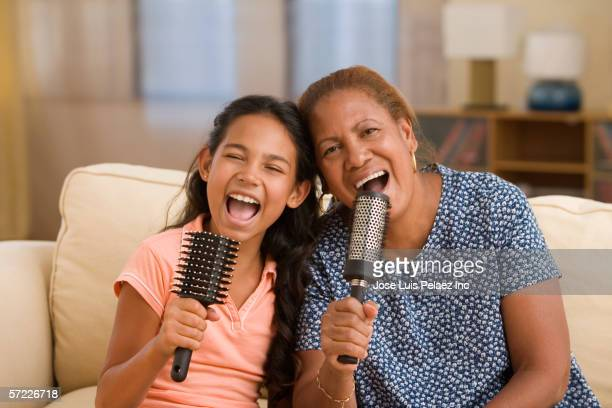 Mother and daughter singing into their headphones