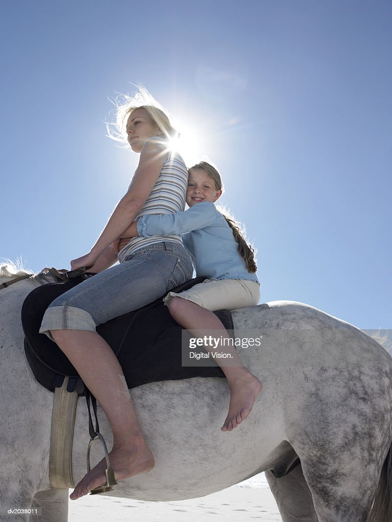 Mother and Daughter Sit on a White Horse, Backlit by the Sun : Stock Photo