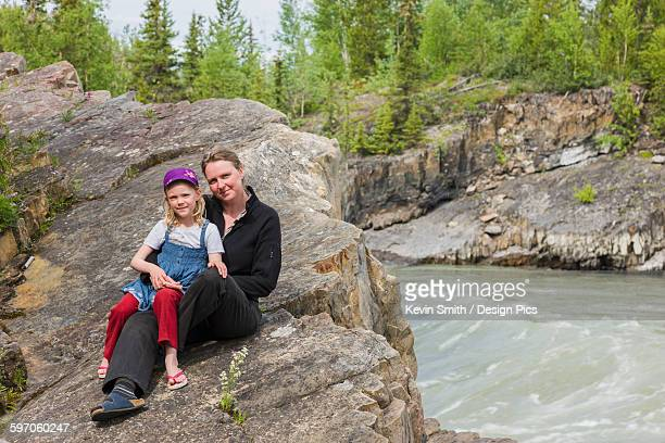 a mother and daughter sit on top of whirlpool canyon along the liard river, alaska highway, north of liard hot springs, british columbia, canada, summer - hot women pics ストックフォトと画像