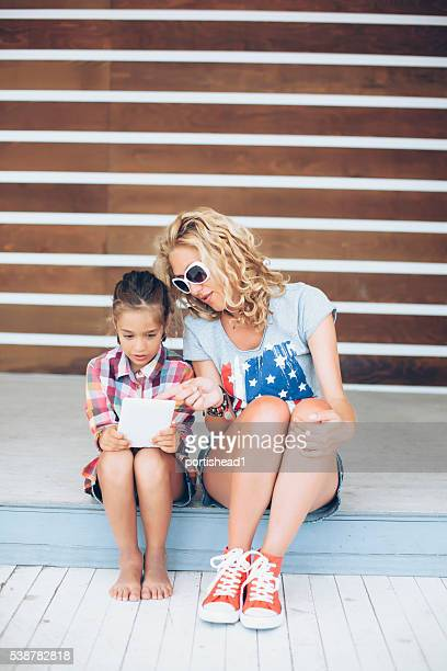 Mother and daughter sitting and using digital tablet