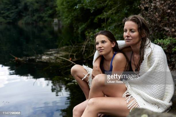 mother and daughter sitting at a lake wrapped in a blanket - wearing a towel stock pictures, royalty-free photos & images