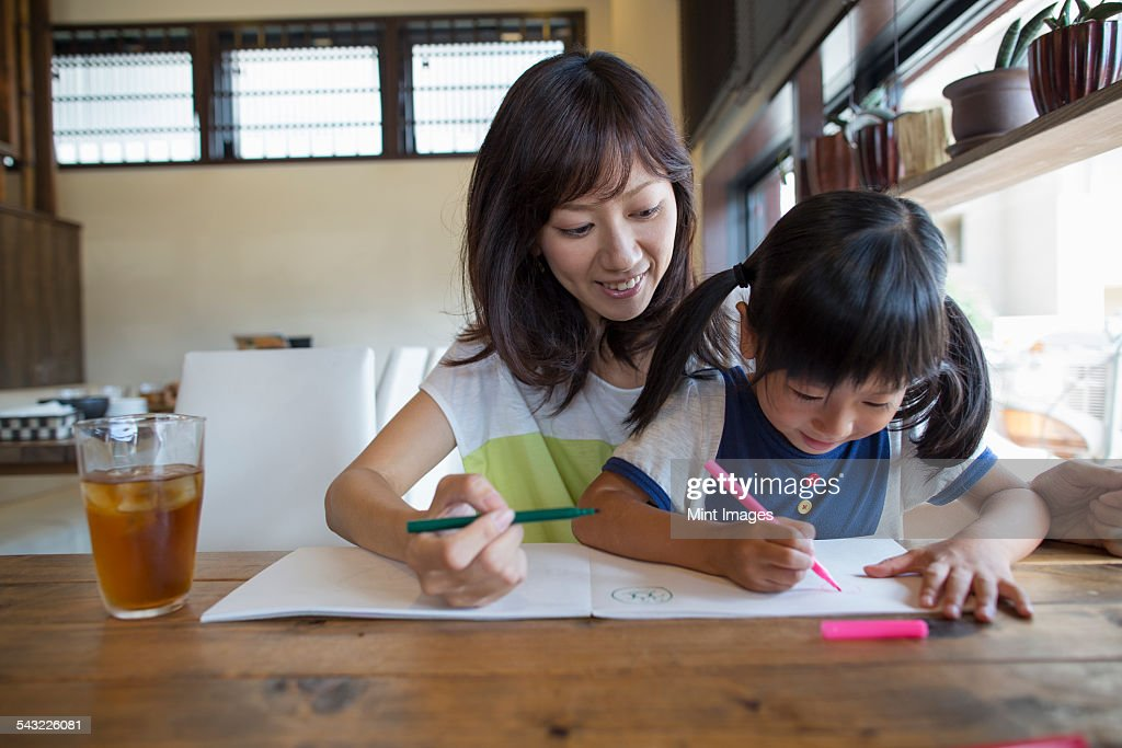 Mother and daughter sitting at a table, drawing with felt tip pens, smiling. : Stock Photo