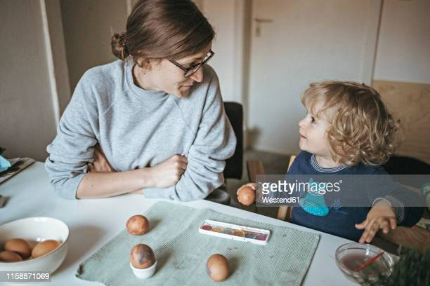 mother and daughter sitting at table at home painting easter eggs - happy easter mom ストックフォトと画像