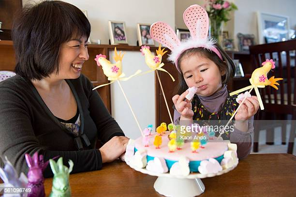 Mother and daughter sitting at table, Easter cake in front of them