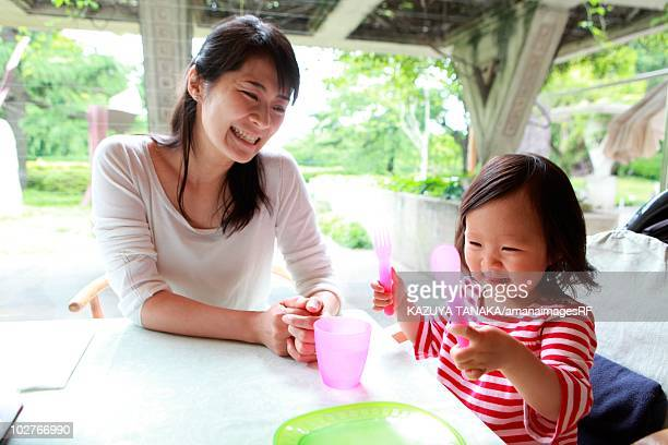 Mother and daughter sitting at table waiting for food