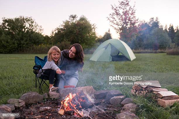 mother and daughter sitting beside campfire, cooking sausage over fire - mother and daughter smoking stock photos and pictures