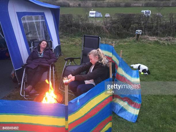mother and daughter sitting by a fire on a campsite - windbreak stock pictures, royalty-free photos & images