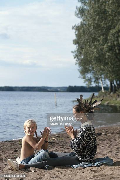 Mother and daughter (6-7) sitting by river playing