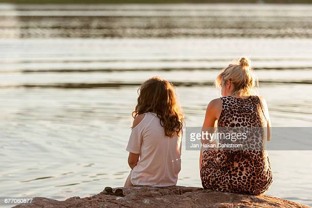 Mother and daughter sitting by the sea