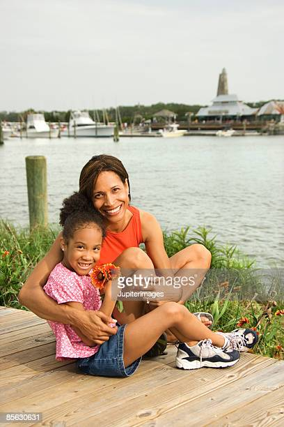 Mother and daughter sitting by water