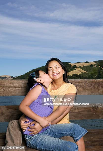 mother and daughter (10-11 years) sitting by wooden balustrade - 10 11 years stock pictures, royalty-free photos & images