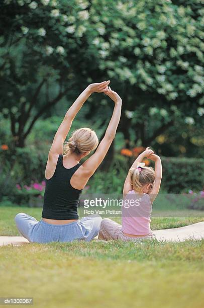 Mother and Daughter Sitting Crosslegged Stretching Arms Above Head, Rear View