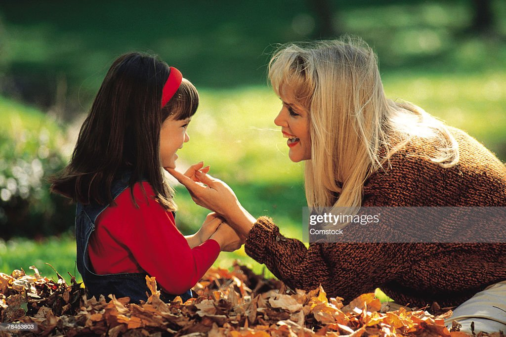 Mother and daughter sitting in a pile of leaves : Stockfoto