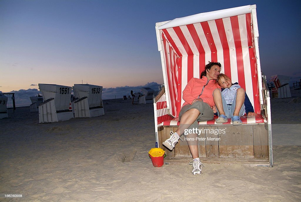 mother and daughter sitting in beach chair : Stockfoto