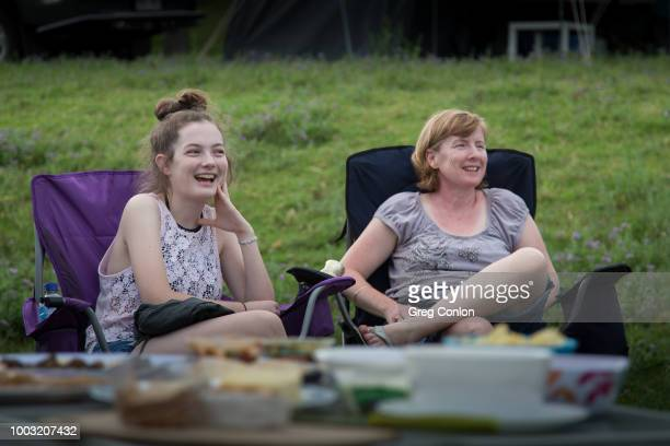 Mother and Daughter sitting in camping chairs, smiling in conversation