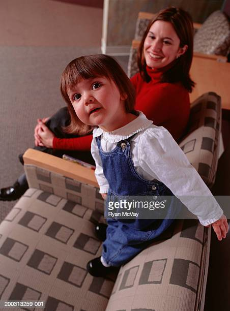 Mother and daughter sitting in clinic waiting hall, (3-4)