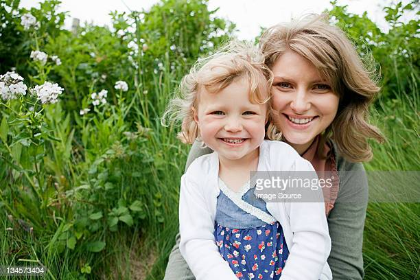 Mother and daughter sitting in field, looking at camera
