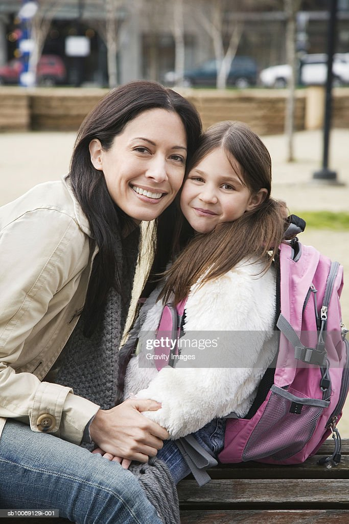 Mother and daughter (8-9) sitting in park, smiling, portrait : Stockfoto