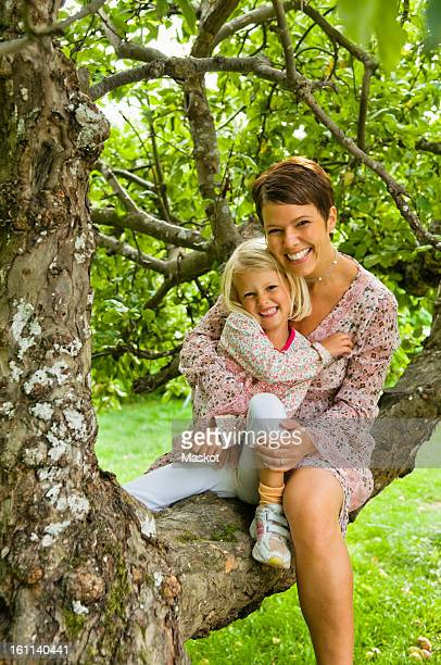 mother and daughter sitting in tree - thick girls stock photos and pictures