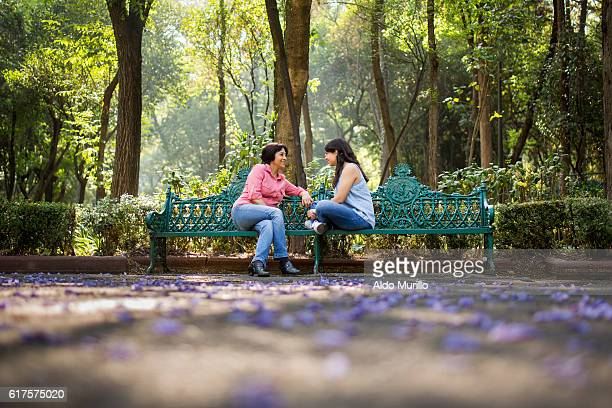 Mother and daughter sitting on a bench at the park