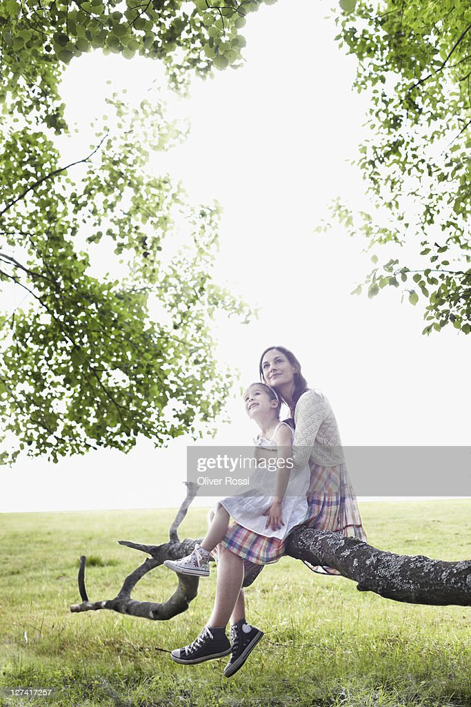 mother and daughter sitting on a branch : Stock Photo