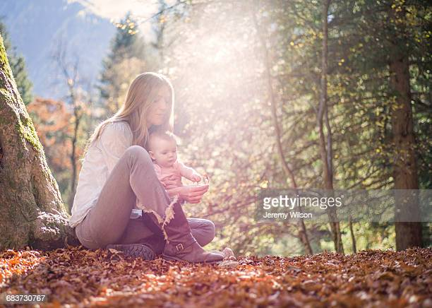 Mother and daughter sitting on autumn leaf covered forest floor
