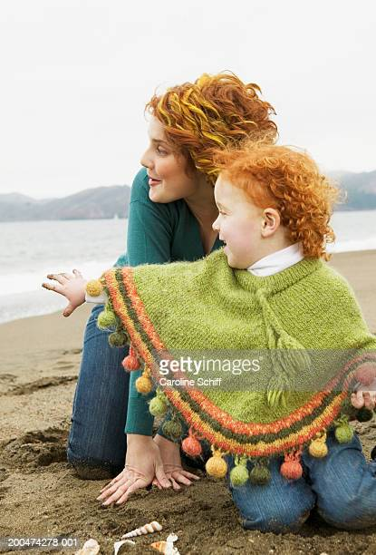 mother and daughter (2-4) sitting on beach, looking out toward sea - caroline roux photos photos et images de collection