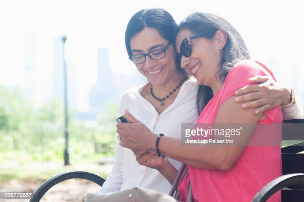 Mother and daughter sitting on bench outdoors posing for cell phone selfie